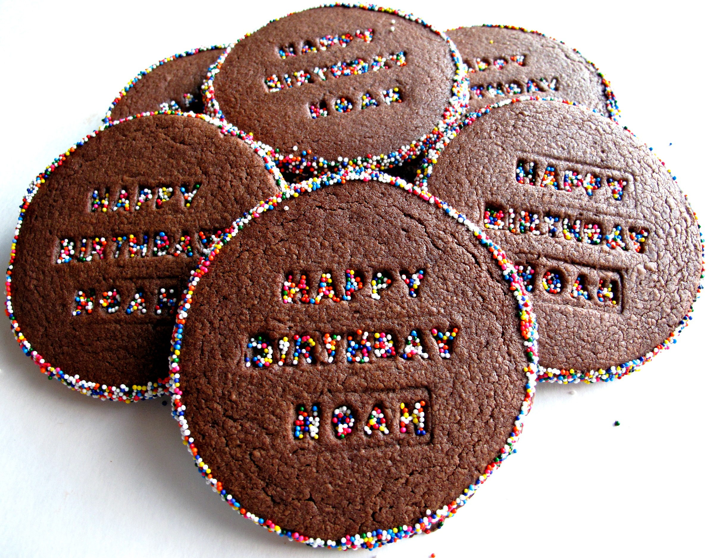 Chocolate cookies with multicolored sprinkles around the edges and on the imprinted words on each cookie.