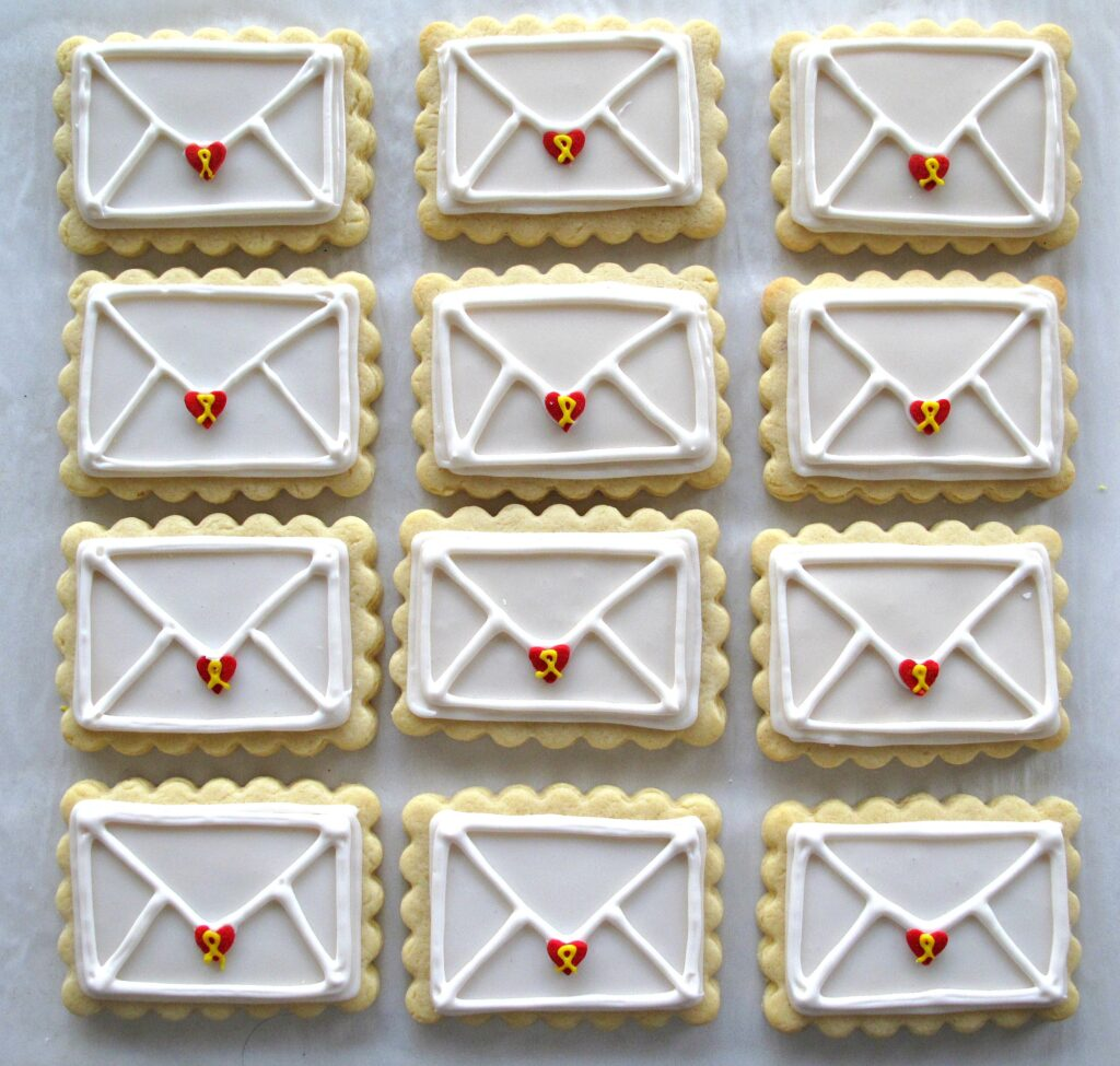 Rows of 12 Valentine Envelope Sugar Cookies, rectangular sugar cookies with a scalloped edge iced white with white lines piped on top to look like the back of an envelope. At the tip of each envelope flap is a red heart sprinkle that has a yellow icing ribbon piped on it.