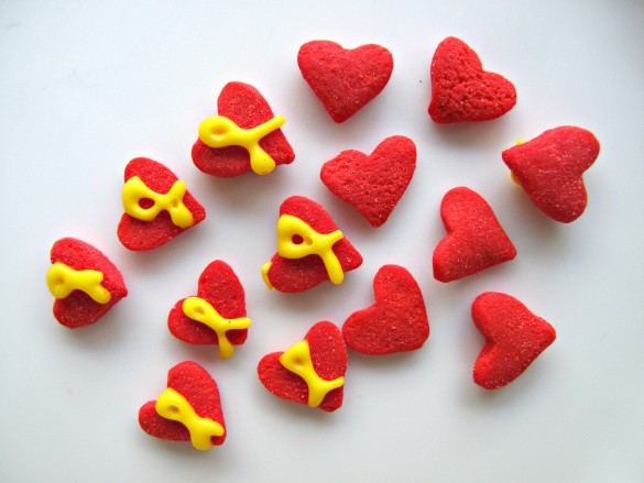"""Red heart sprinkles each with a yellow """"support our troops"""" ribbons piped on top."""