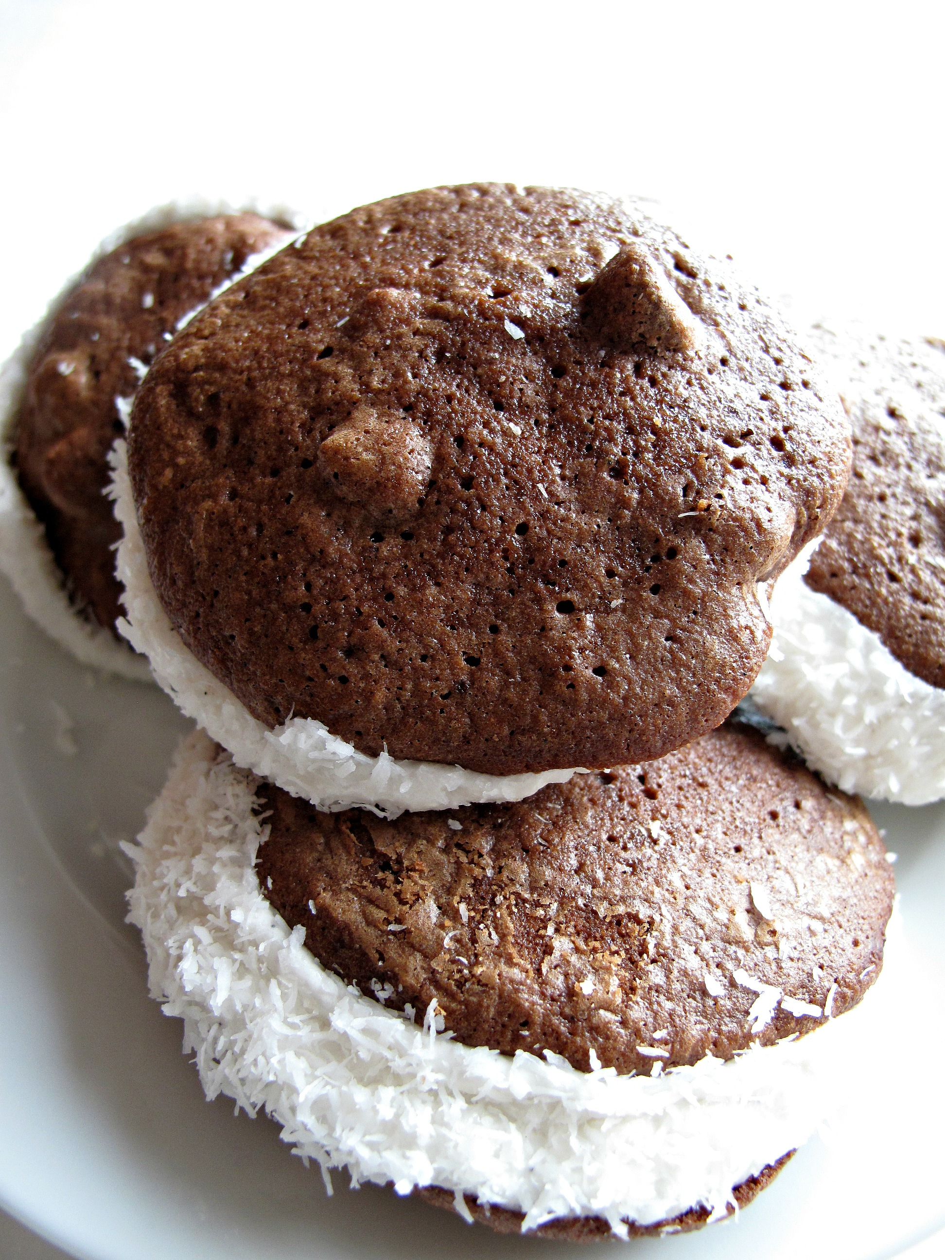 Whoopie Pies with marshmallow filling and edges rolled in coconut.