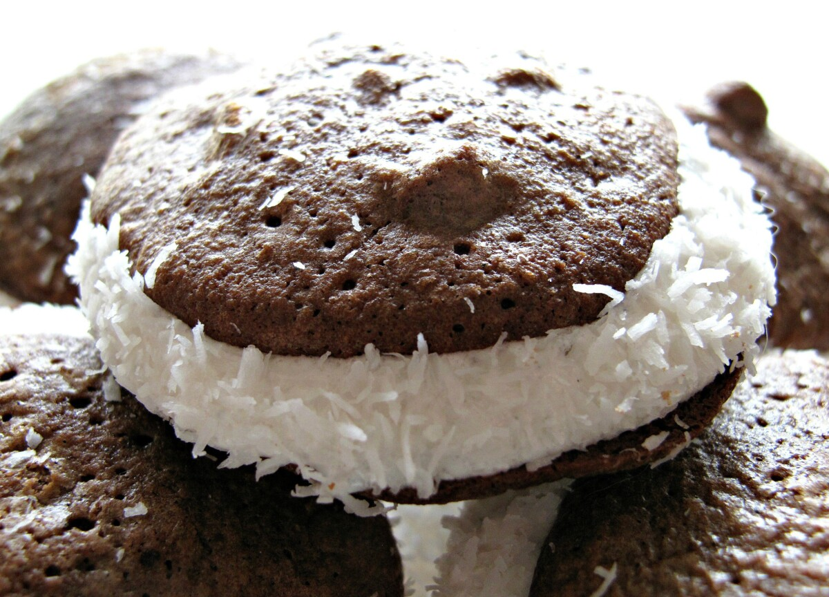 Whoopie Pie closeup showing two flourless chocolate cookies sandwiched with marshmallow cream and coconut edges.