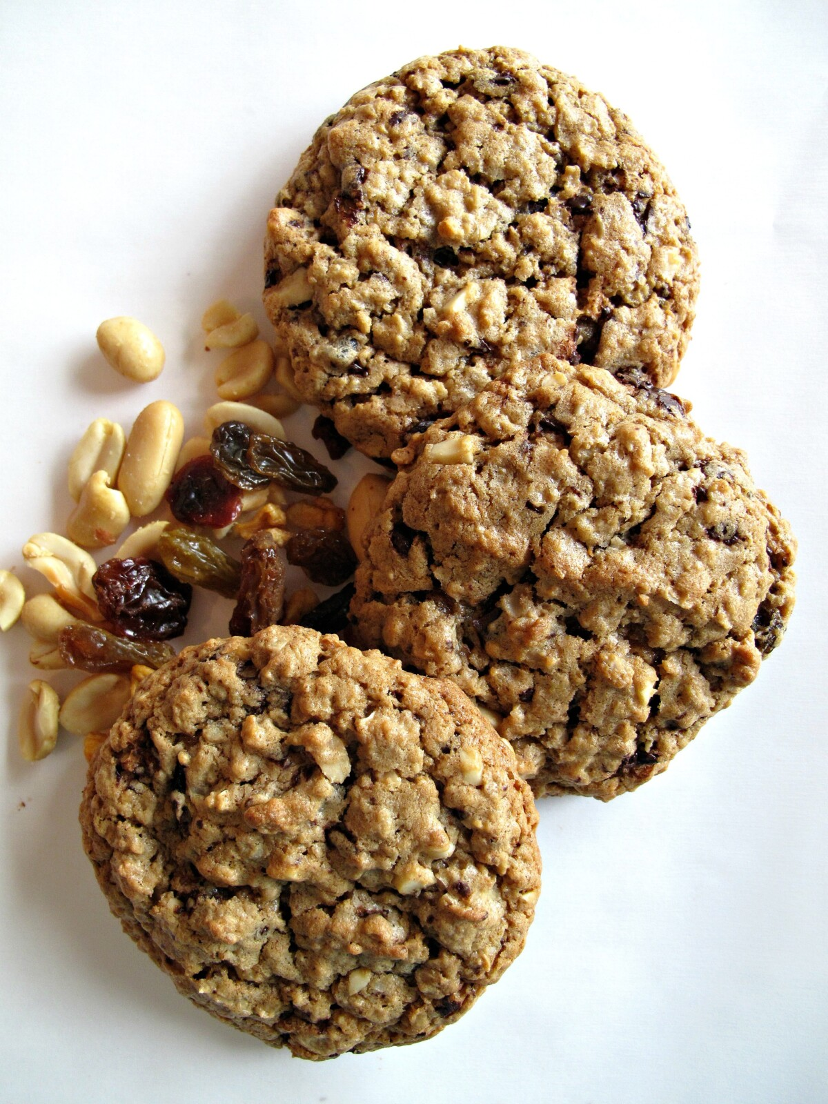 Three thick, crackled Marathon Cookies next to some peanuts and dried fruit.