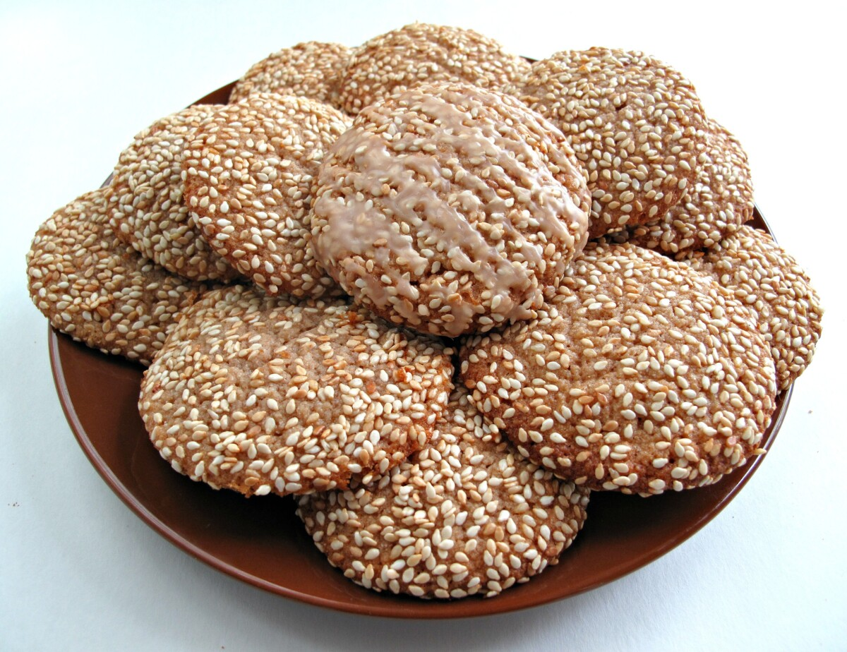 Sesame seed covered cookies on a brown serving plate.