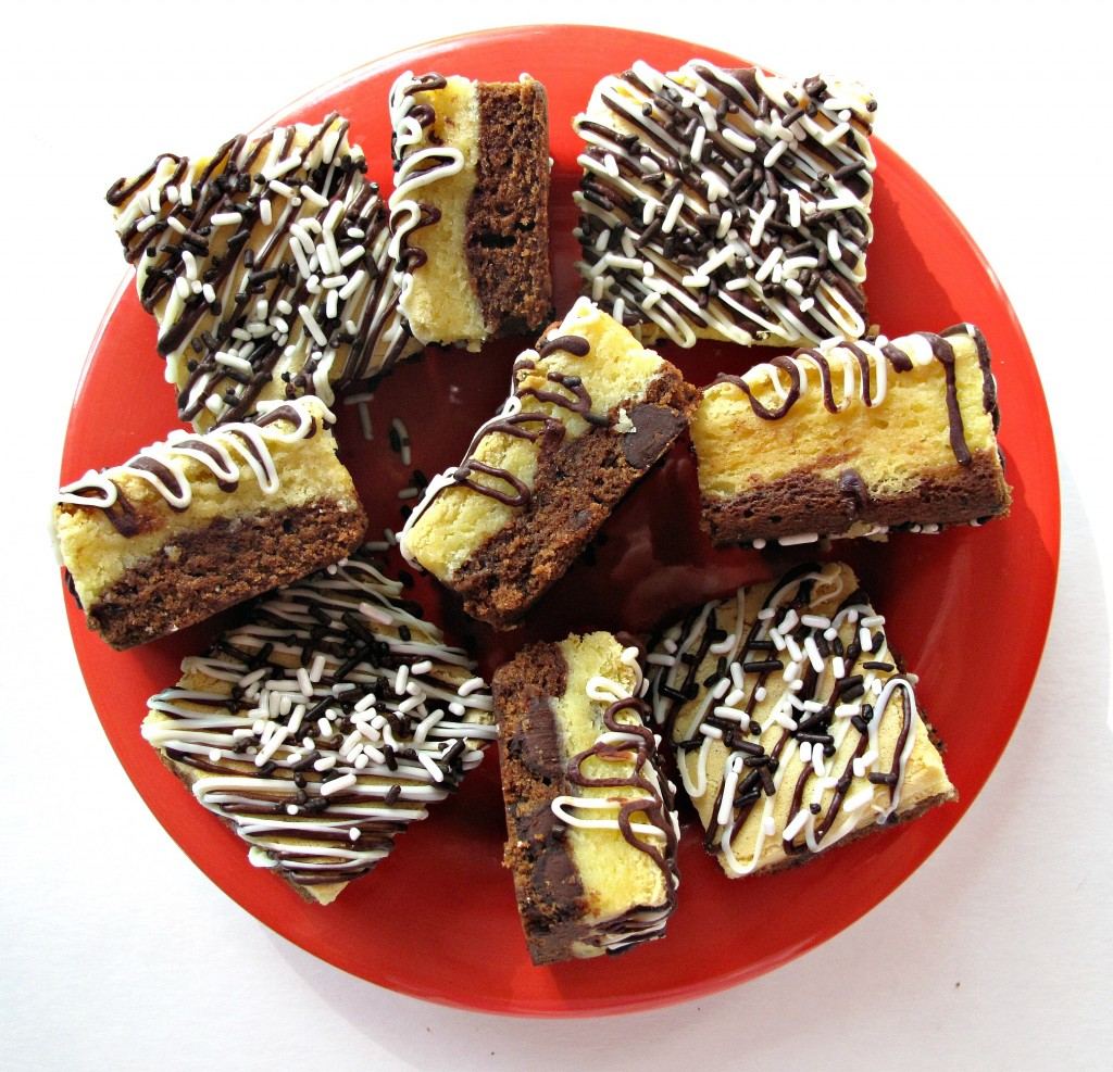 Black and White Bars on a red plate. The bars have a white chocolate blondie layer on top and a brownie layer on the bottom. The tops of the square bars are covered with diagonal stripes of white and dark drizzled chocolate and white and brown jimmies sprinkles.