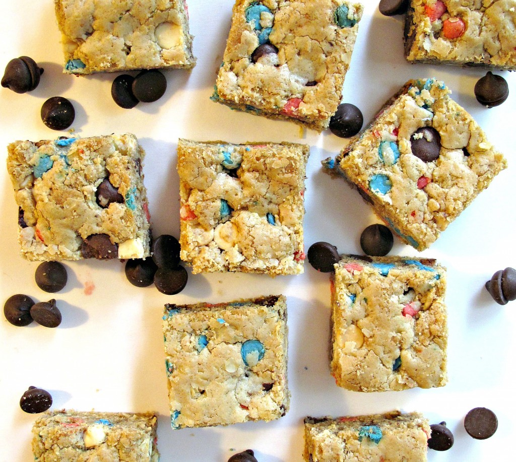 Chocolate Chip Oatmeal Cookie Bars are oatmeal brown with red, blue, and chocolate chips peaking through the dough.
