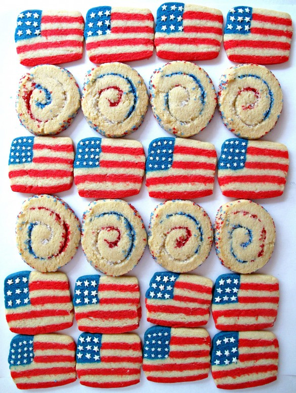 Rows of cookies. Flag cookies have red and white stripes with a blue square in the corner. White star sprinkles are stuck onto the blue square. Round cookies with red, white and blue sugar swirled inside look like sparklers.