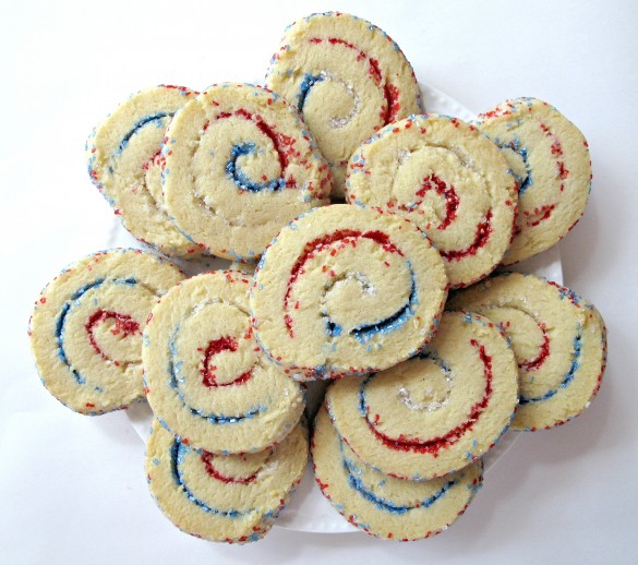 Spiral Sparkler Cookies on a platter. The cookies have white dough that is sprinkled with red,white,blue sparkling sugar, then rolled up and sliced into cookies.