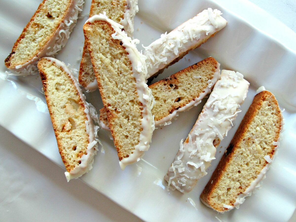 Biscotti topped with white chocolate and shredded coconut on a white platter