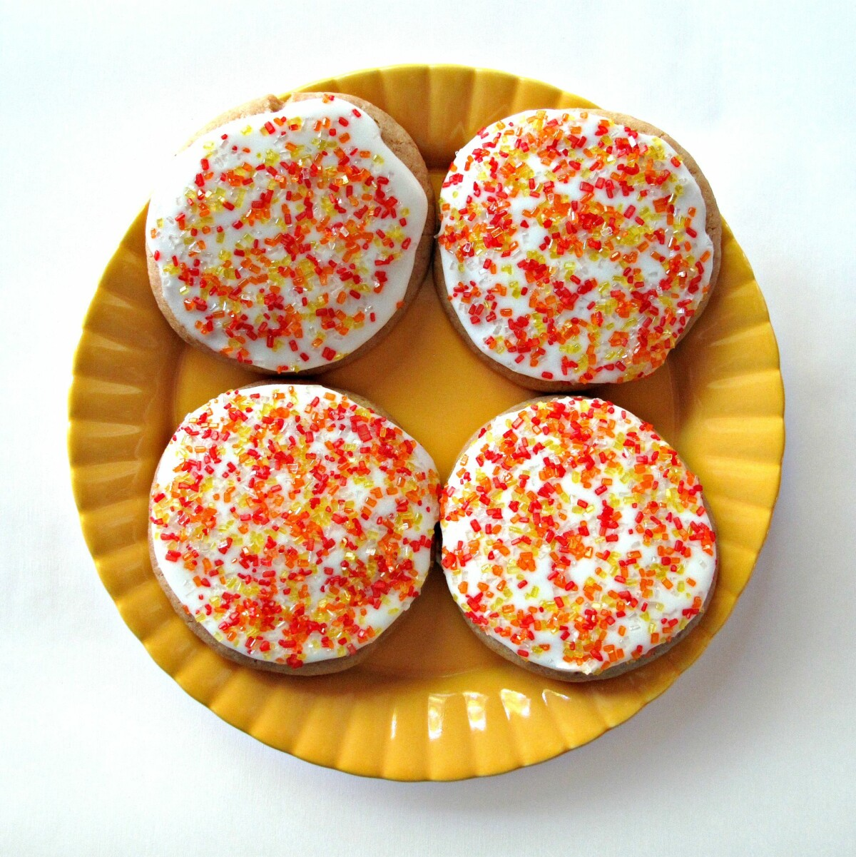 Four iced cookies with yellow and red sprinkles on a yellow plate.