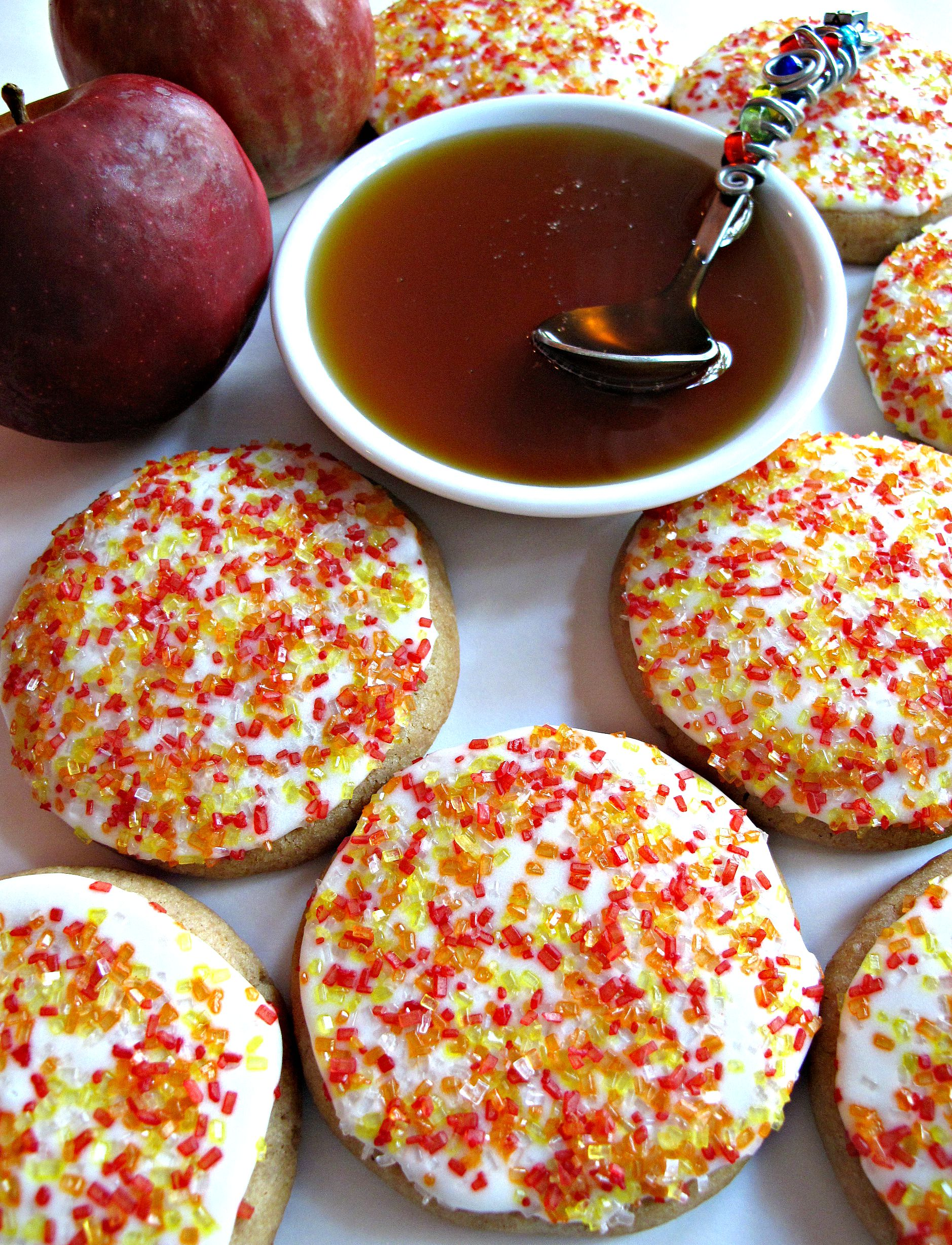 Iced cookies with yellow and red sugar sprinkles with a honey bowl and two apples.