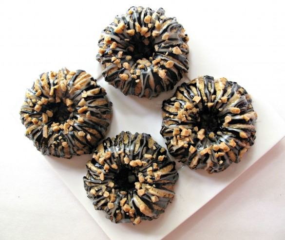 Vanilla Bean Mini-Bundt Cakes with Chocolate-Toffee Crunch- fluffy vanilla bean cake and a crunchy chocolate-toffee filling under a double drizzle of chocolate and vanilla icing. | The Monday Box
