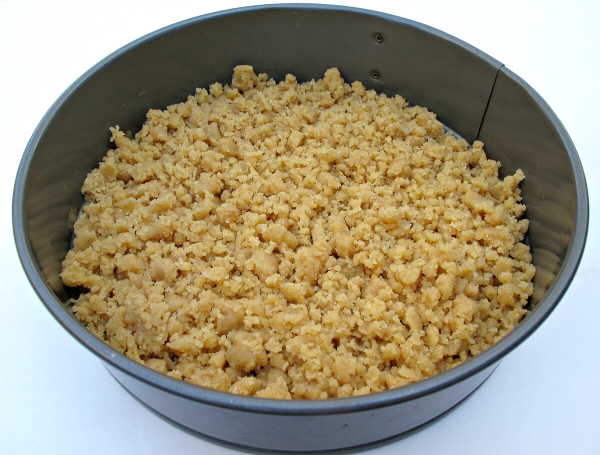 Streusel crumbs packed into the bottom of a round springform cake pan.