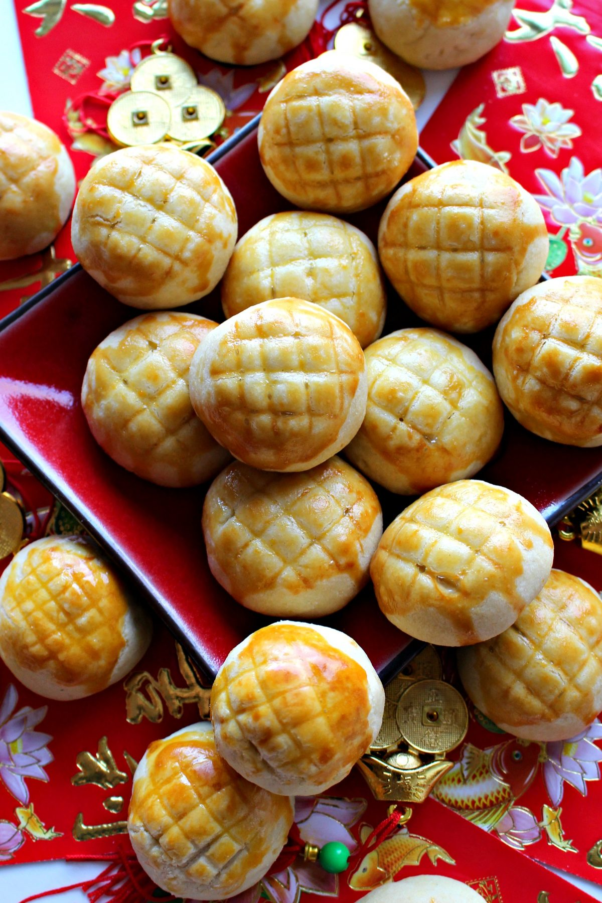 Ball shaped Pineapple Cookies on a red plate surrounded by  red and gold New Years decorations.