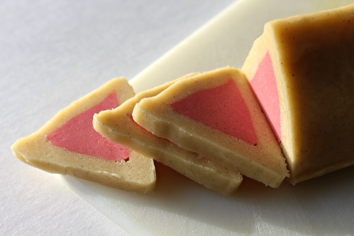Closeup of triangle dough log with pink triangle center being sliced.