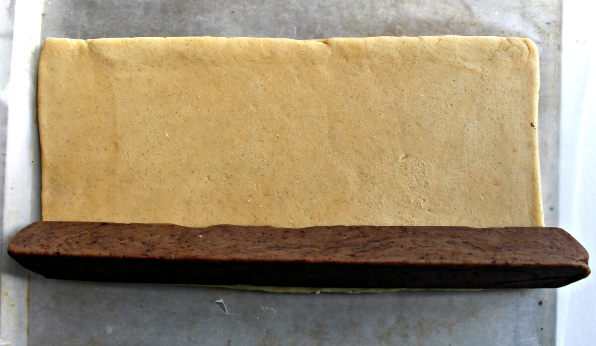 Triangle log of chocolate dough on top of flat rectangle of vanilla dough.