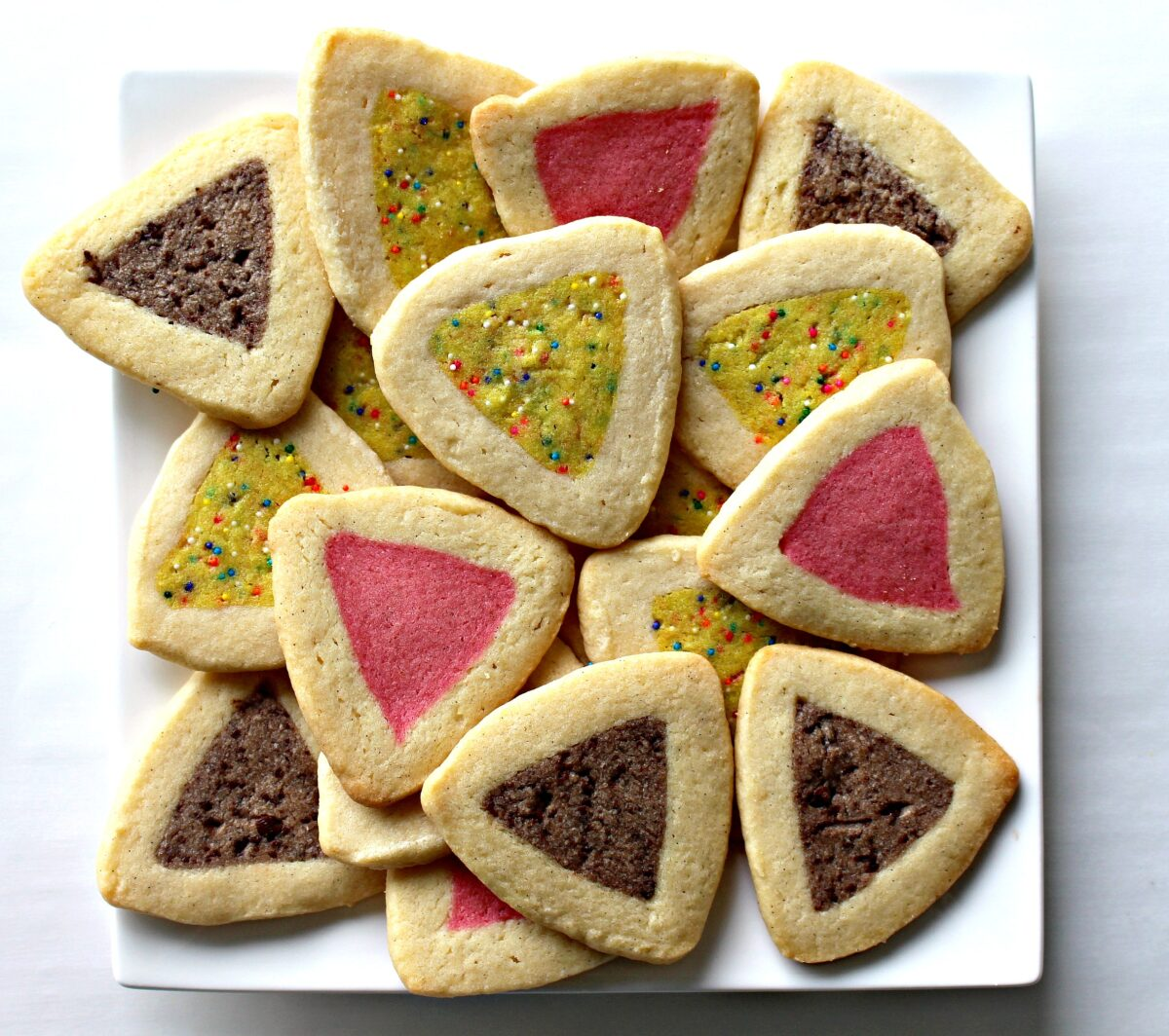 Triangle Hamantaschen, buttery sugar cookies with flavored and colored centers in brown, pink, and yellow.