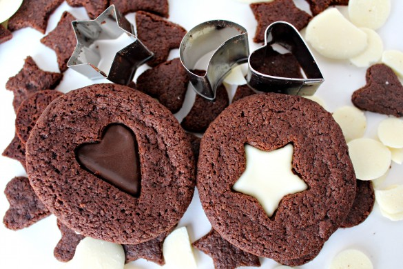 2 Chocolate Mint Sandwich Cookies one with dark chocolate filling showing through heart cutout and one with white chocolate filling showing through star cutout