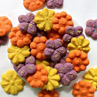 Cookie Press Butter Cookies are flower shaped and springtime pretty. These melt-in-your-mouth morsels are just right for Mother's Day or any time you want to share some baked love. A SURPRISE INGREDIENT makes these cookies quick, easy, AND delicious!   The Monday Box