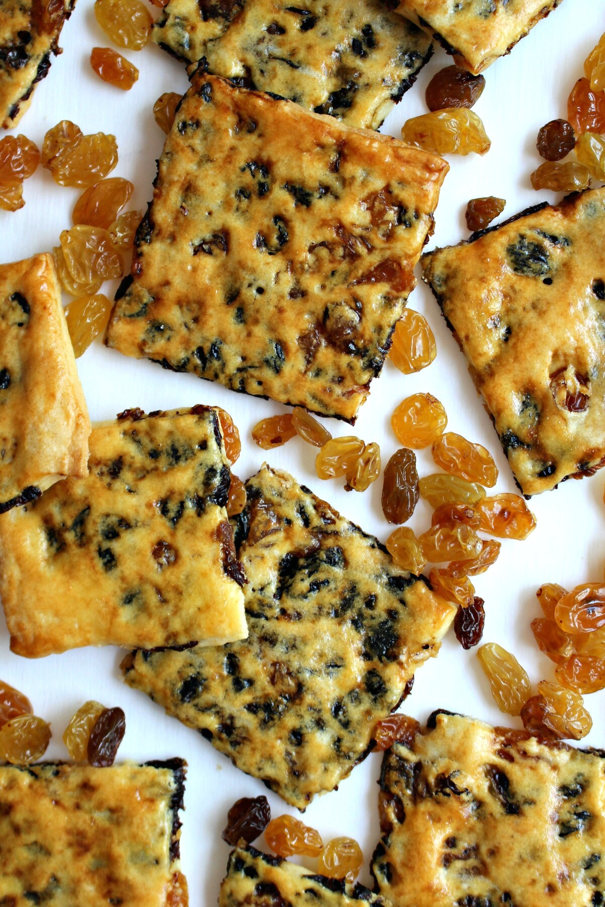Thin cookie squares with raisins showing through the crust on a white background.