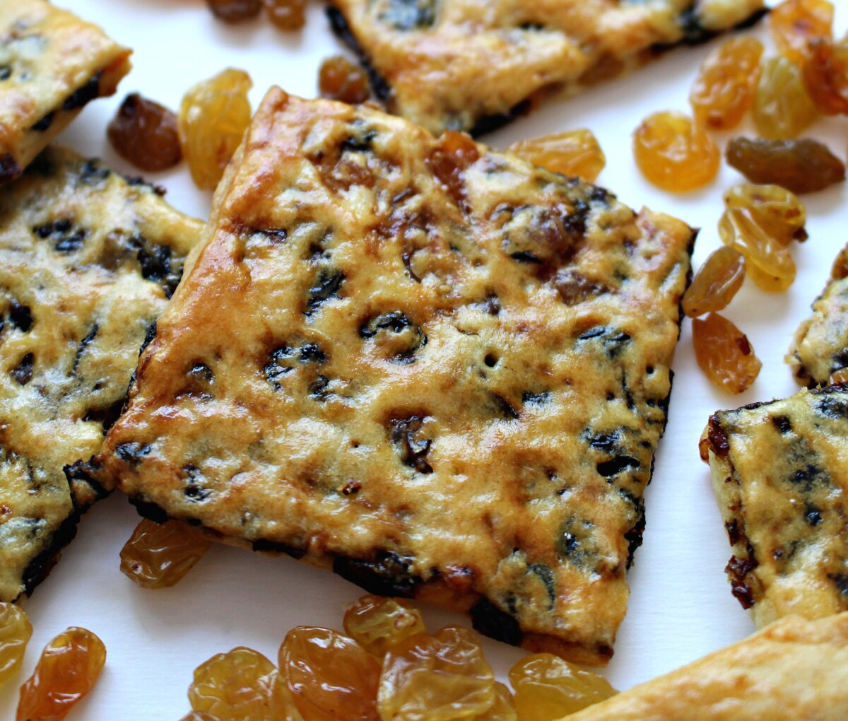 Closeup of a thin raisin cookie square showing the shiny golden crust.
