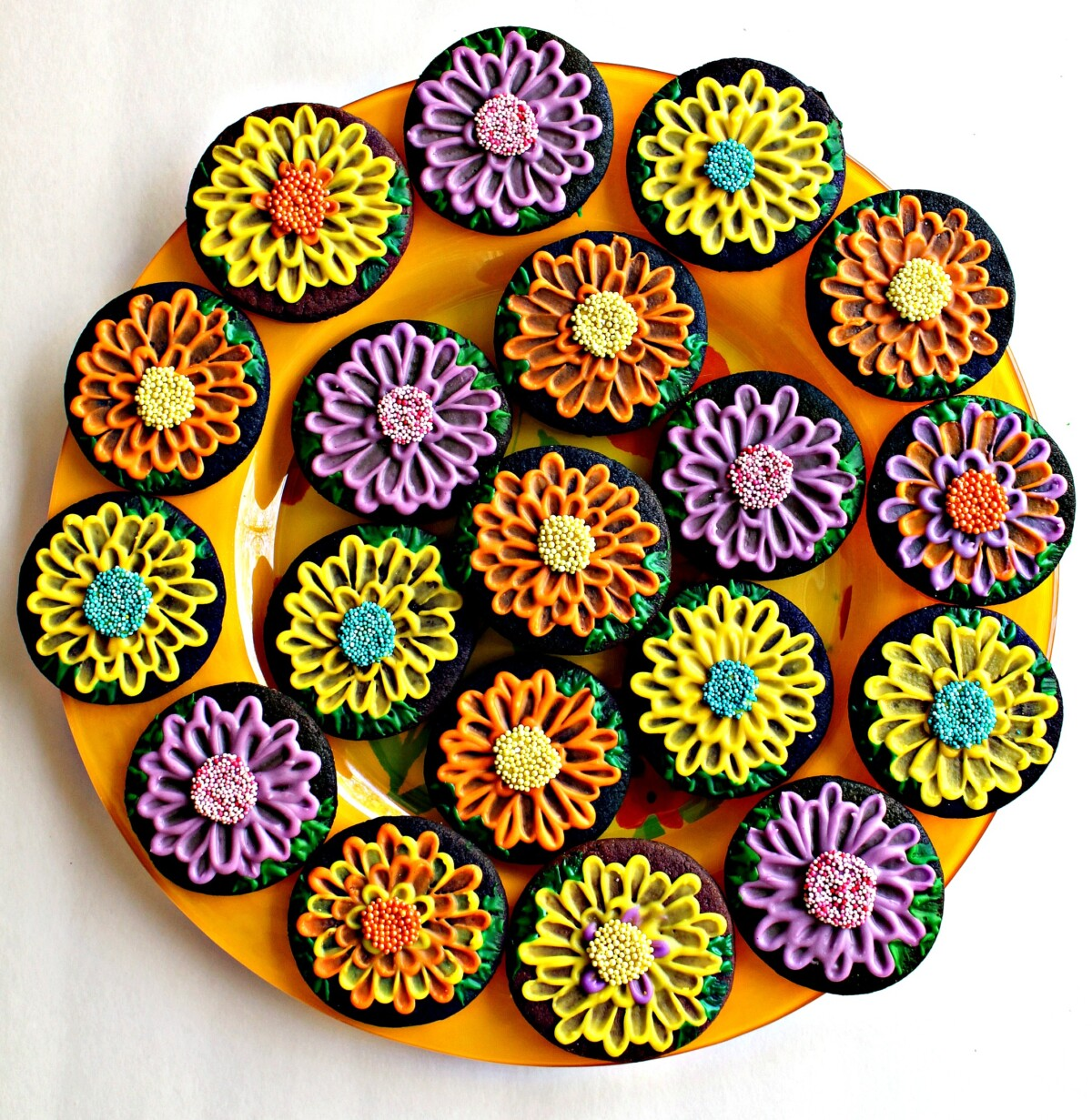 May Flowers Sugar Cookies  in many colors on a round, yellow platter.