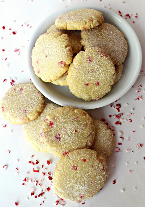 Lemon Peppermint Cooler Cookies, round cookies speckled with pieces of peppermint candy and dusted with fine white sugar, in a bowl and on a white surface sprinkled with bits of red and white peppermint candy.