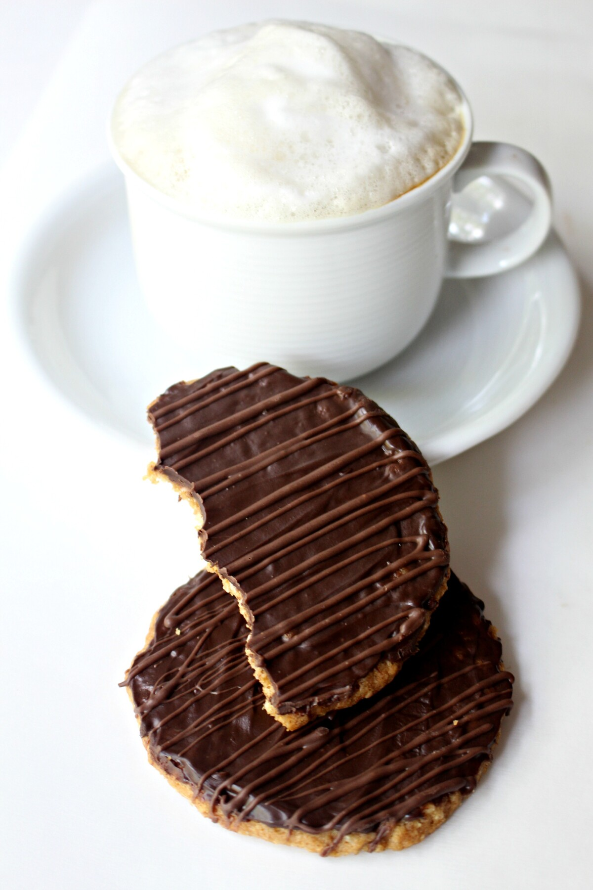 Two cookies in front of a white mug of cappuccino topped with milk foam.