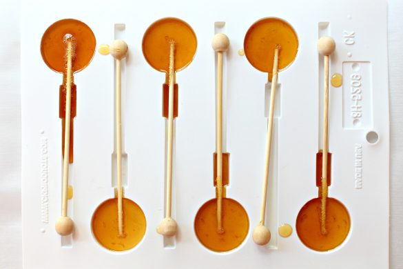 White plastic mold for circle lollipops with the golden lollipop syrup in the circles and wooden stick inserted in each one.