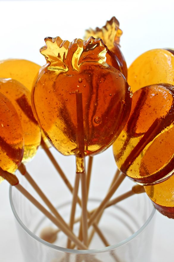 Honey Lollipops are a golden amber color in molded in circle shapes and apple shape with wooden sticks.