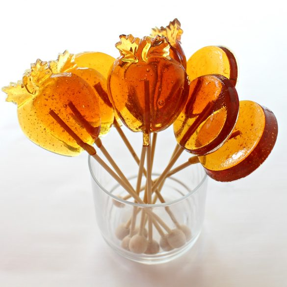 Honey Lollipops made in apple shaped molds and circle molds with wooden sticks propped in a clear glass to give as Rosh Hashanah gifts.