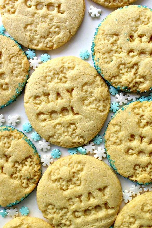 """Stay Cool Imprinted Cookies, round sugar cookies stamped with snowflakes and the words """"stay cool"""", on a white surface with blue and white snowflake sprinkles."""