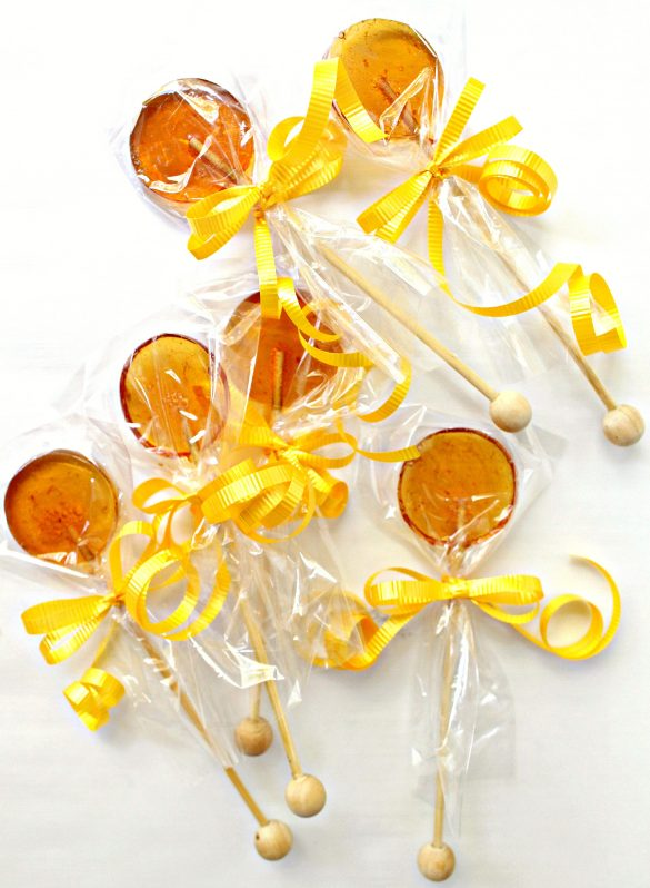 Honey Lollipops with cellophane bags over the candy, tied with a yellow ribbon.