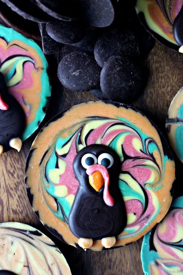 Chocolate Bark Thanksgiving Turkey made in a round muffin tin with swirled colored chocolate in the background and a dark chocolate turkey head and body piped on top. The turkey has candy eyes and beak with piped on colored chocolate waddle and feet