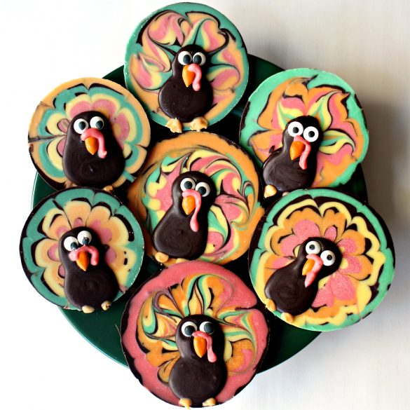 Chocolate Bark Thanksgiving Turkeys in many different colors on a green serving plate.