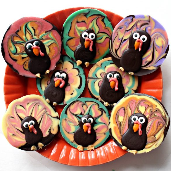 Chocolate Bark Thanksgiving Turkeys in many colors on an orange serving plate.