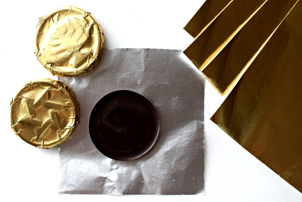 Homemade Chocolate Coins (Chanukah Gelt) lying on gold foil for wrapping