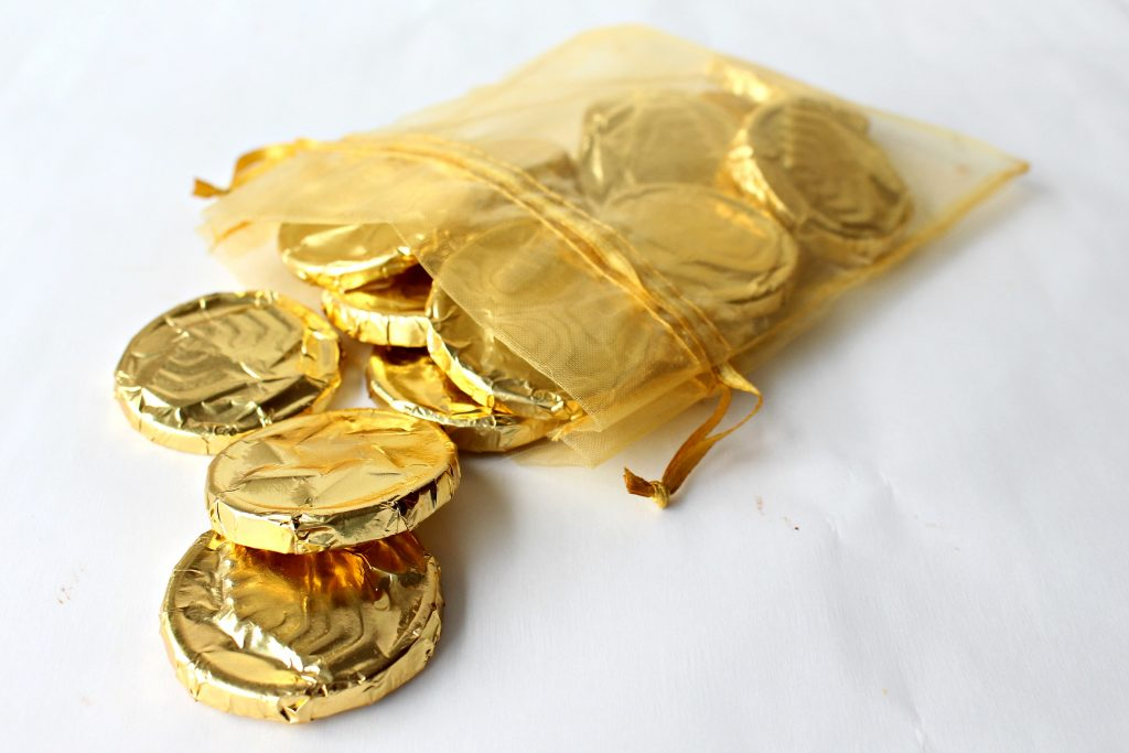 Homemade Chocolate Coins (Chanukah Gelt) spilling out of a gold mesh bag