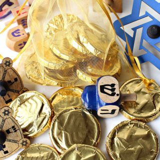 Gold foil wrapped Homemade Chocolate Coins (Hanukkah Gelt) with small, wooden dreidels
