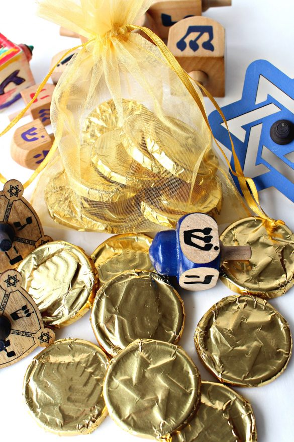 Homemade Chocolate Coins (Chanukah Gelt)in a gold mesh bag and dreidles