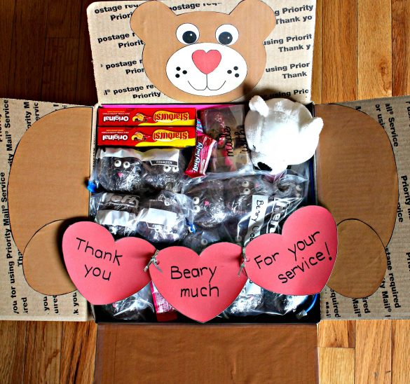 "Thank You Beary Much Military Care Package is decorated inside with the head of a bear on the top flap, arms and paws on the side flaps hold a red heart garland across the box. The garland says,"" Thank you beary much for your service!"""