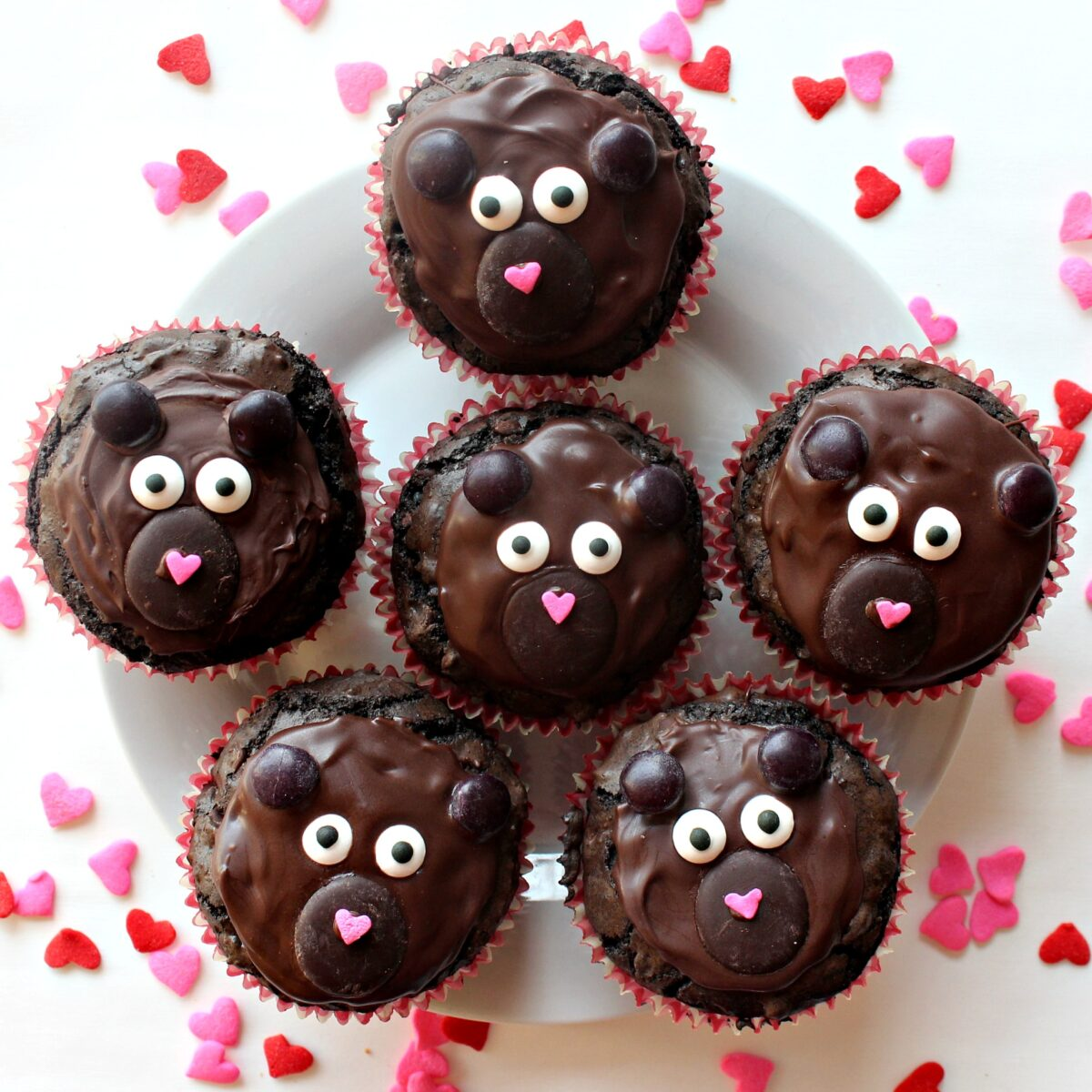 Brownie bears cupcakes on a white plate, surrounded by heart sprinkles.