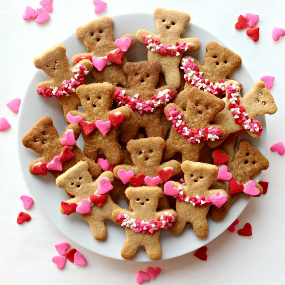 Honey Graham Bears on a white plate each holding a garland of sprinkle hearts.