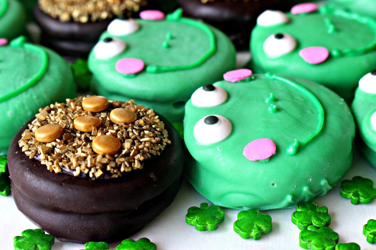 Closeup of a chocolate covered cookie decorated like a pot of gold and a frog.