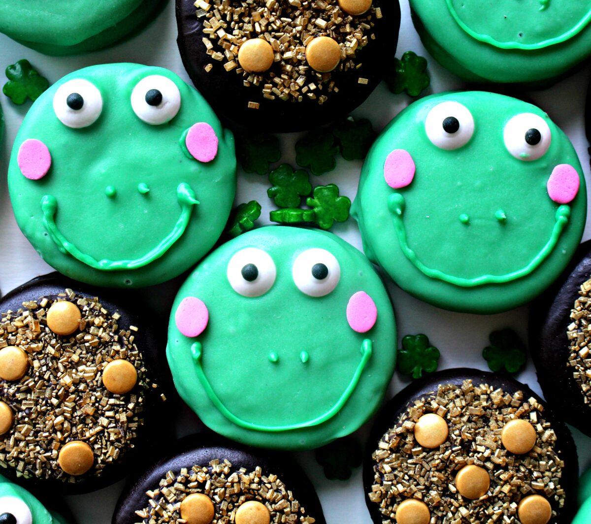 Closeup of green coated cookies decorated like frogs.
