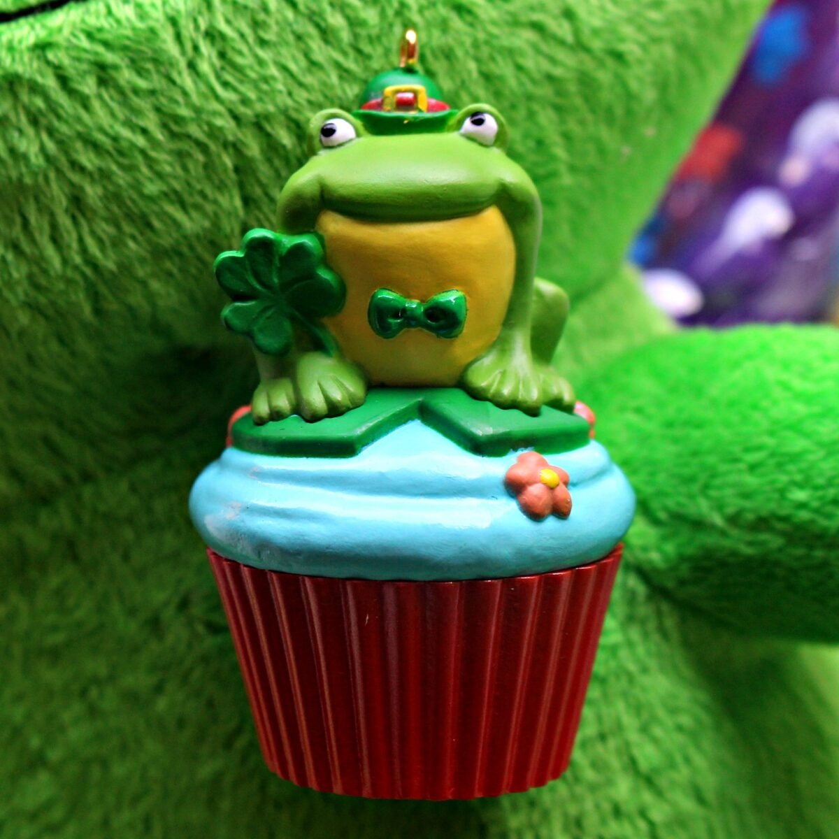 An ornament of a frog sitting on a blue frosted cupcake in a red cupcake holder.