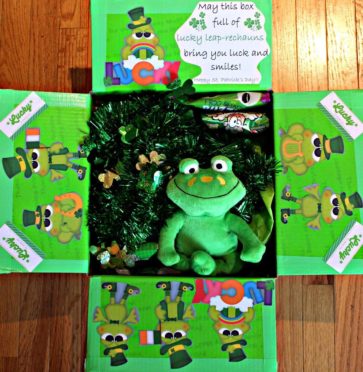 A care package box with flaps decorated with green cartoon frogs and a stuffed frog inside.