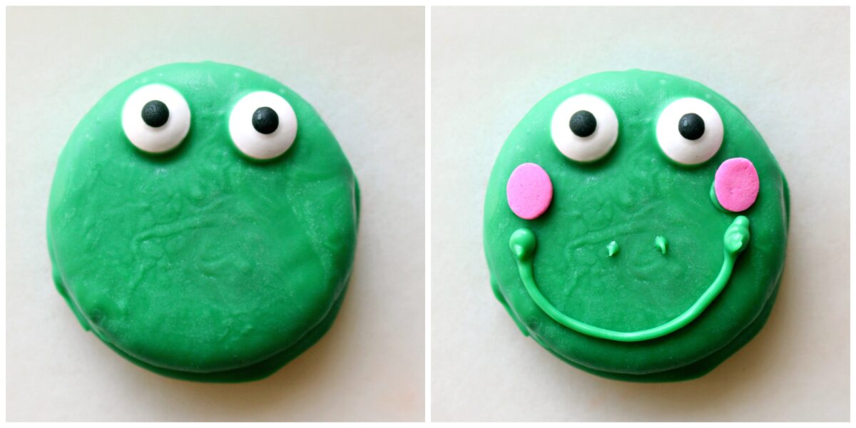 Green coated cookie with candy eyes and with green piped mouth and pink sprinkle cheeks.