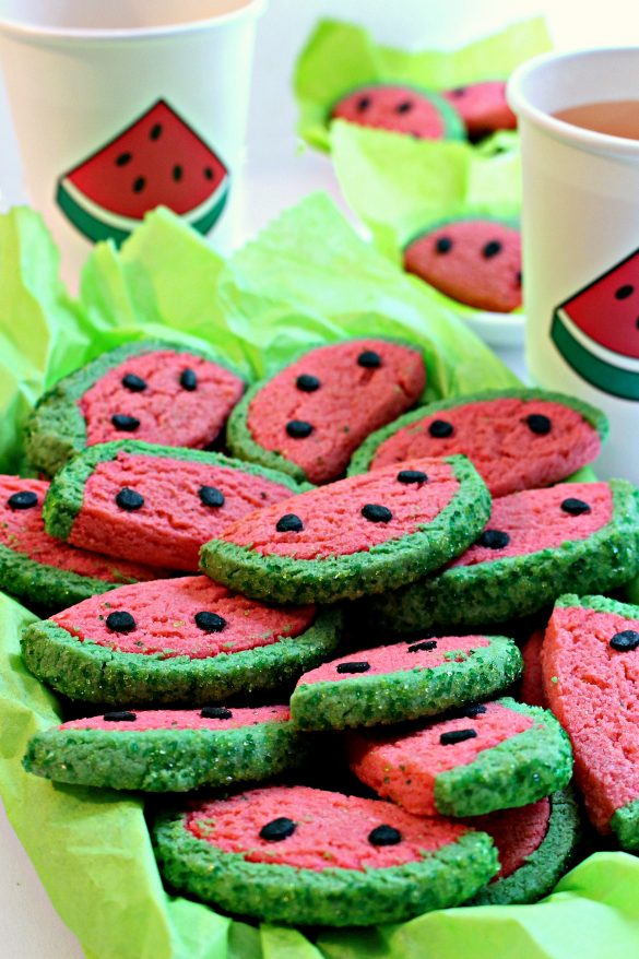 "Watermelon Sugar Cookies in a serving dish lined with bright green tissue paper. The cookies are half circles that look just like slices of watermelon. They are bright pink with a green ""rind"" edge and three black ""seeds"" all made of colored cookies dough."