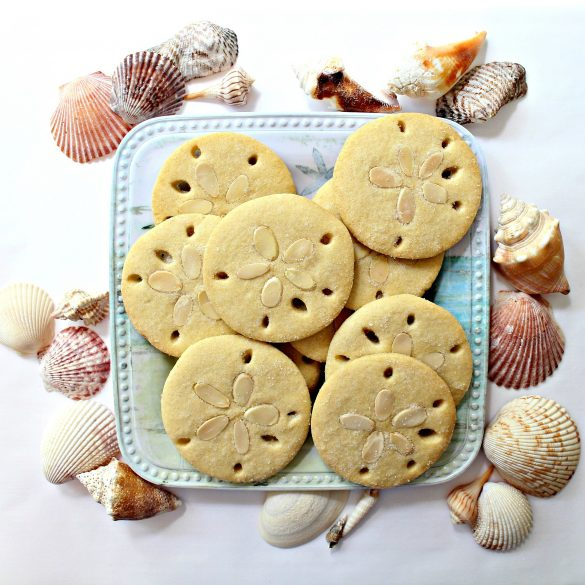 Almond Sand Dollar Cookies are almond flavored sugar cookies decorated to look like sand dollars with 5 holes around the edges and 5 almond slices in pressed into the center of each cookie in a flower formation.