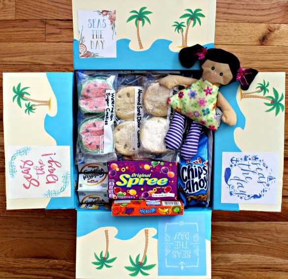 Seas the Day! A Day at the Beach care package with inside flaps decorated to look like the beach with blue paper waves and palm trees.
